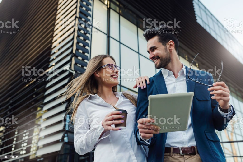 Businessman and businesswoman standing in the street with digital tablet and coffee stock photo