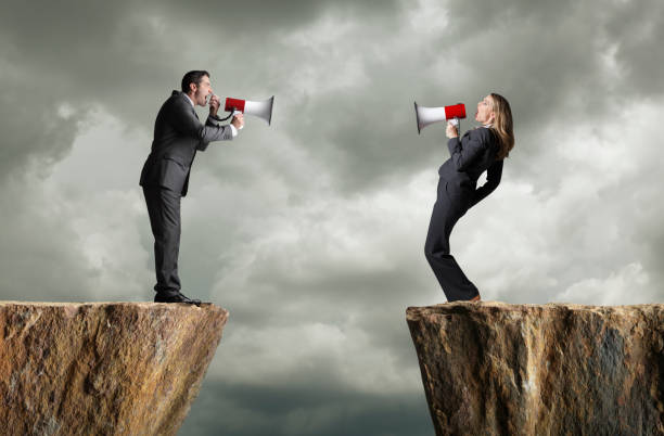 Businessman And Businesswoman Standing On Opposite Cliffs Shout At Each Other stock photo