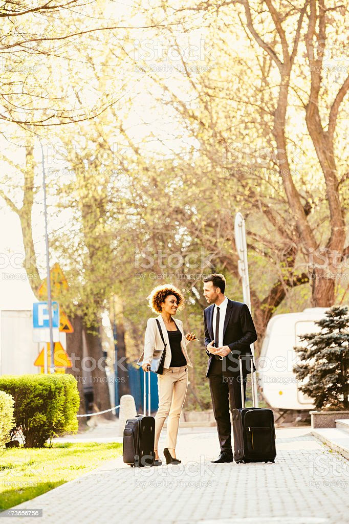 Businessman and businesswoman standing outdoor with suitcases Businessman and afro american businesswoman in formal outfits on business travel, standing outdoor on the sidewalk and holding suitcases.  2015 Stock Photo