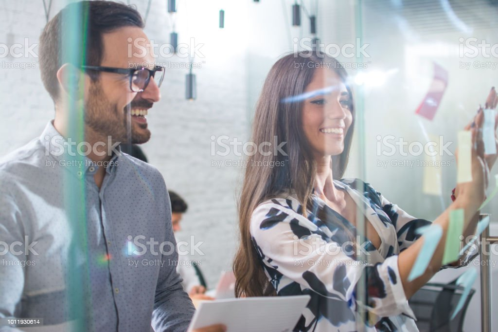 Businessman and businesswoman sticking adhesive notes on glass wall...