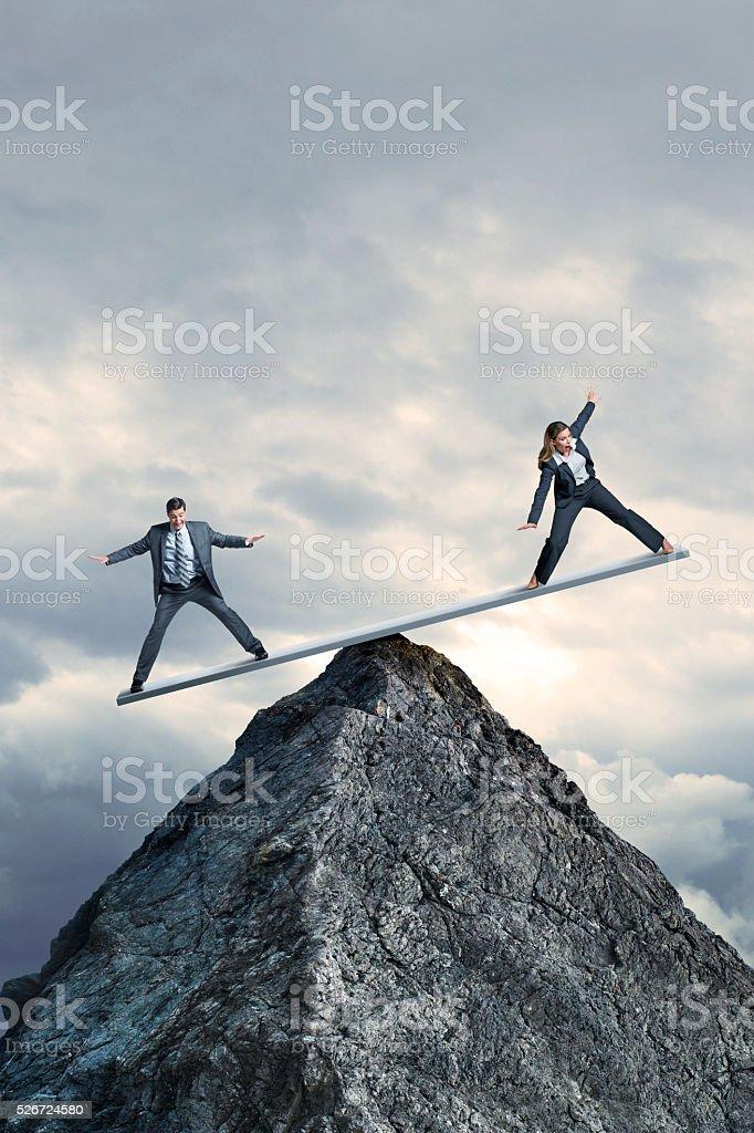 Hombre de negocios y mujer de negocios de lucha para mantener el equilibrio en subibaja - foto de stock