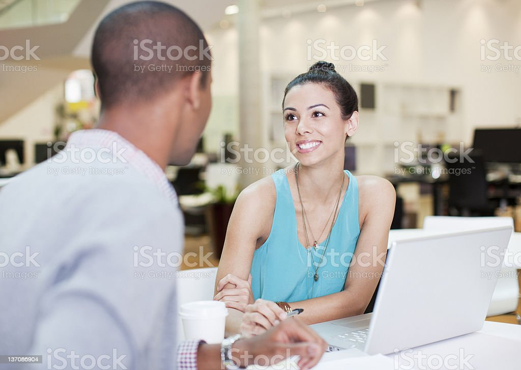 Businessman and businesswoman talking at laptop in office royalty-free stock photo