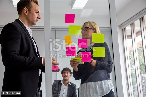 1059655118 istock photo Businessman and Businesswoman tracking tasks on board. Using task control of agile development methodology in the office 1191817344