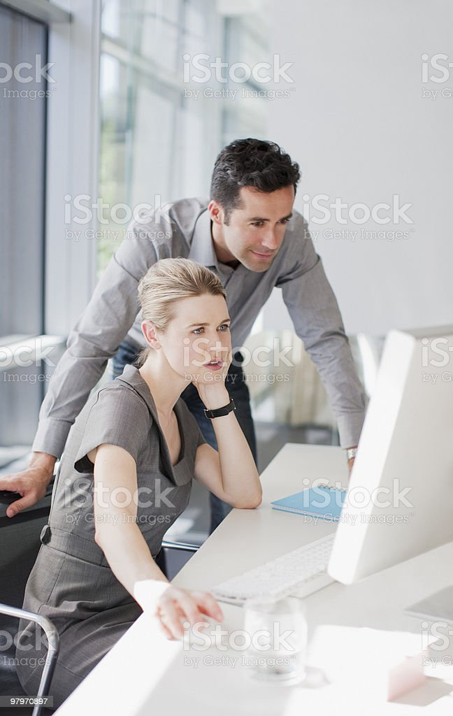Businessman and businesswoman using computer in office royalty-free stock photo