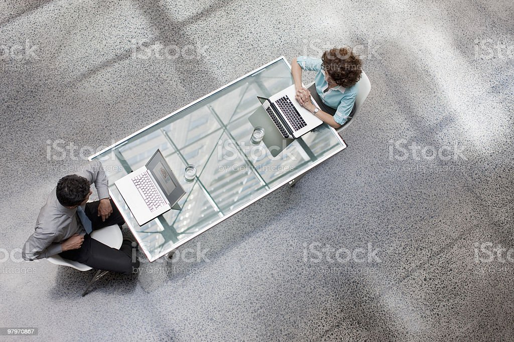 Businessman and businesswoman using laptops at table royalty-free stock photo