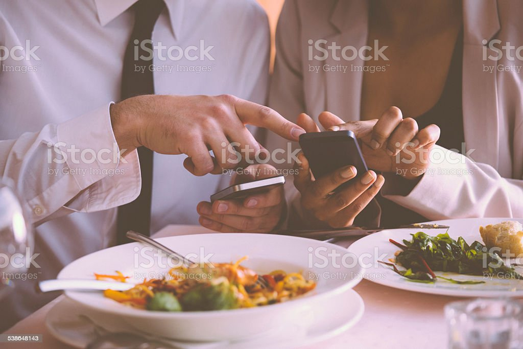 Businessman and businesswoman using phones on lunch Businesswoman and businessman having lunch in the restaurant, using smart phones together. Close up of hands. Unrecognizable person. 2015 Stock Photo