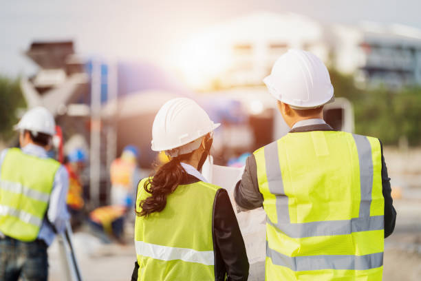 Businessman and businesswoman using see plan paper at construction site stock photo