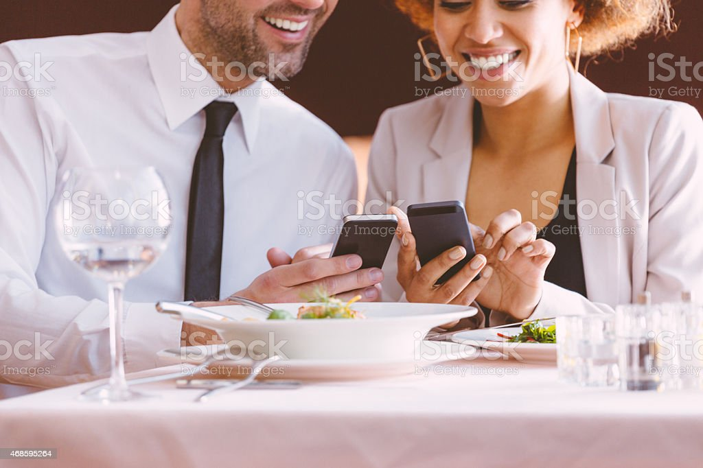 Businessman and businesswoman using smart phones at lunch Afro american businesswoman and caucasian businessman having lunch or dinner in the restaurant, using smart phones together. Close up of smiling faces and hands. Wineglass and plates on the table. 2015 Stock Photo