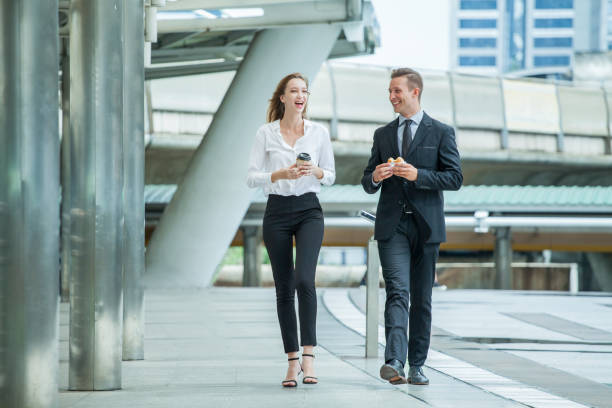 Businessman and businesswoman walking and talking on  street in city Outside Office with ,young couple discussing and eating breakfast , hamburger and drinking coffee together, partners, teamwork stock photo