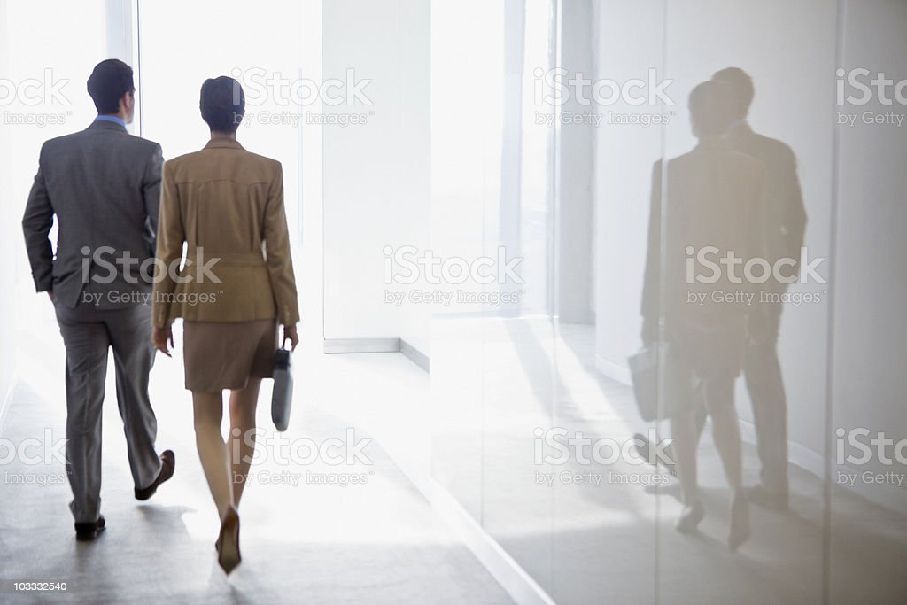 Businessman and businesswoman walking in corridor stock photo