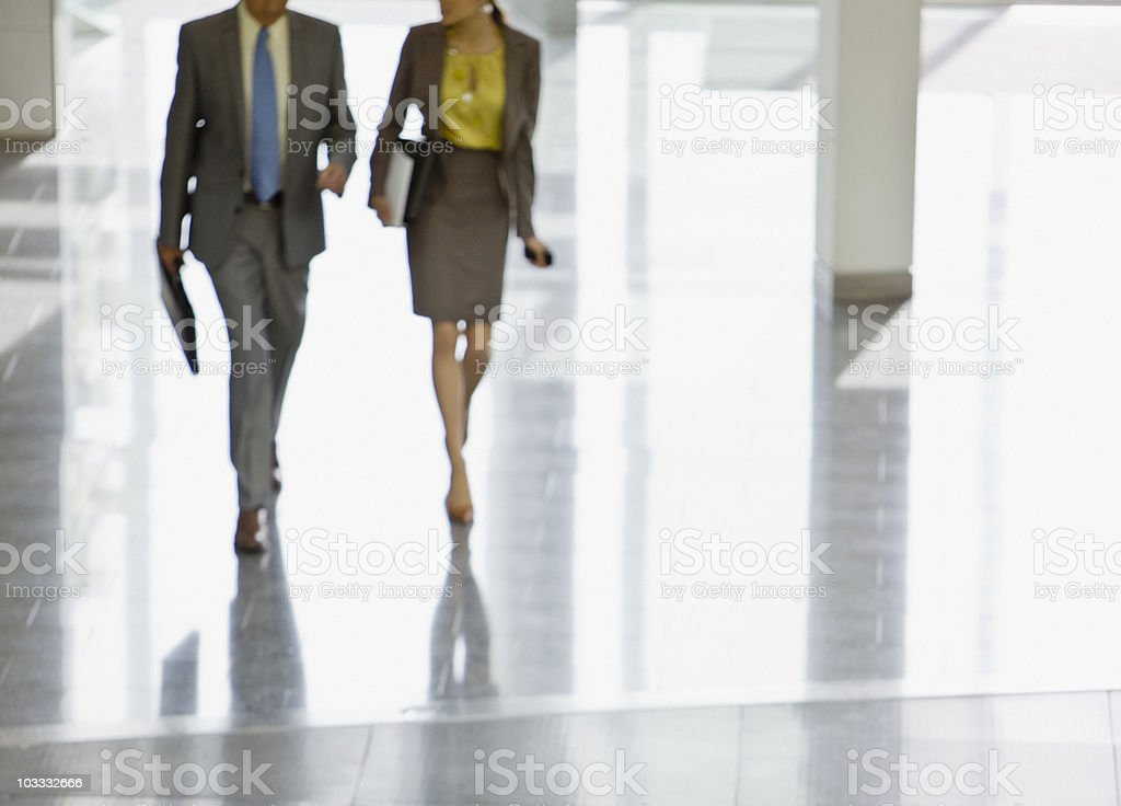 Businessman and businesswoman walking in lobby royalty-free stock photo