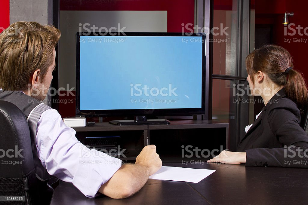 Businessman and Businesswoman with a Video Display in the Office stock photo