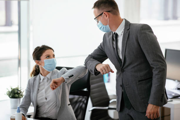 businessman and businesswoman with medical mask in office. - business stock pictures, royalty-free photos & images