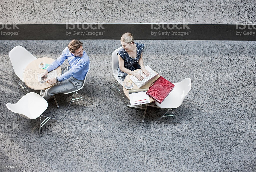Businessman and businesswoman working at tables royalty-free stock photo