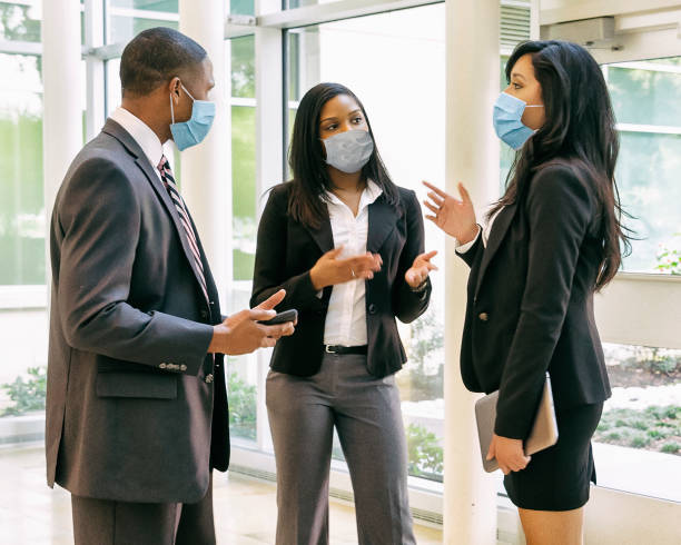 businessman and businesswomen having a meeting wearing face masks. - businessman covid mask foto e immagini stock