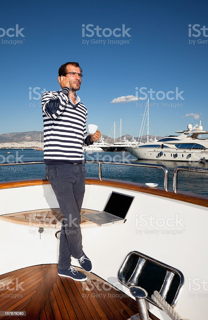 Businessman and captain on board of the yacht having coffee royalty-free stock photo