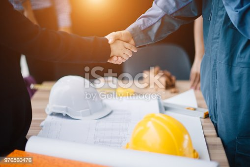 istock Businessman and engineer handshake closing a deal in construction site. Sucessful,engineering and business concept. 976560476