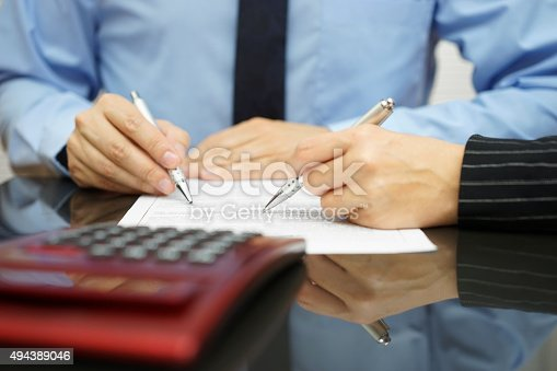 istock businessman and female coworker are examining financial agreement 494389046