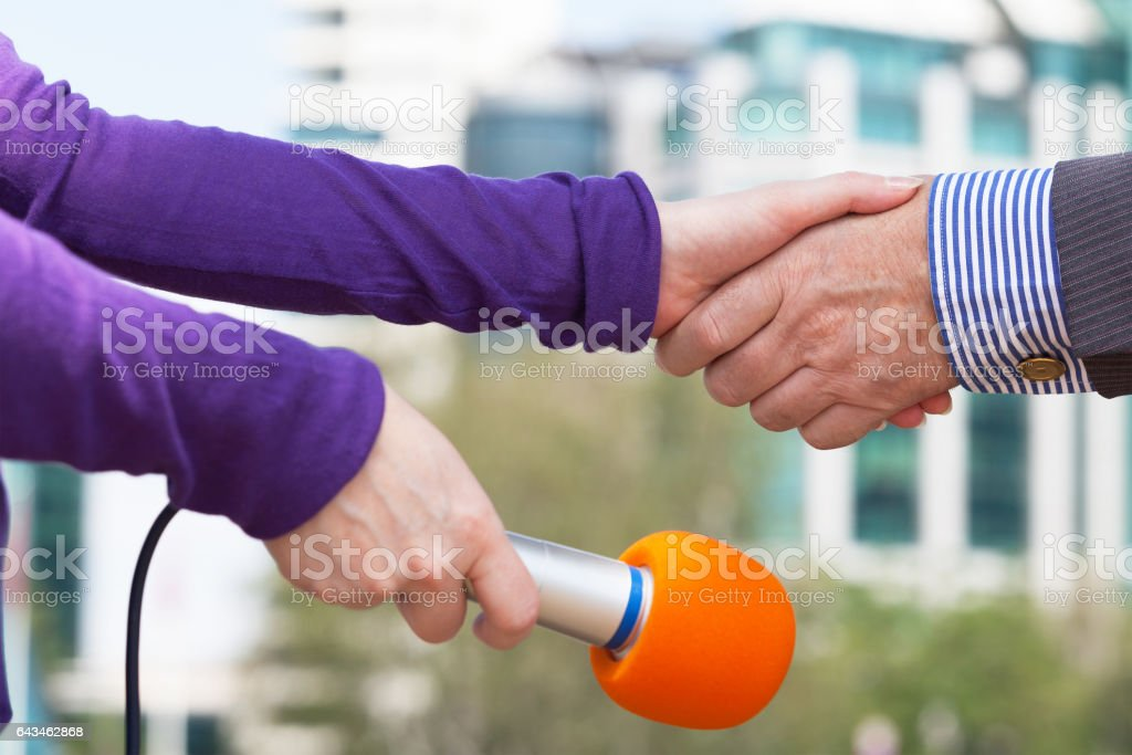 Businessman and female reporter shaking hands before interview royalty-free stock photo