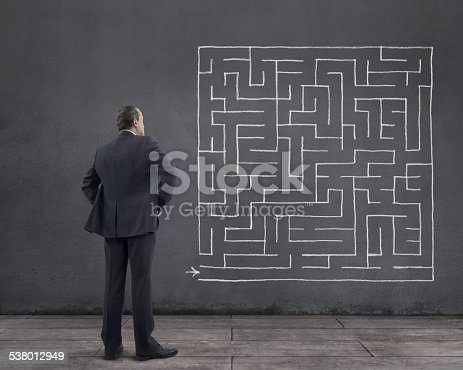 Rear view of businessman standing on wooden floor with maze sketched (chalk drawing) on the wall. He is looking further, thinking, searching new ideas and way to exit.