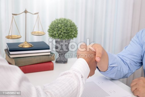 836113188 istock photo Businessman and lawyer handshake to show the success of winning the case. 1145585740