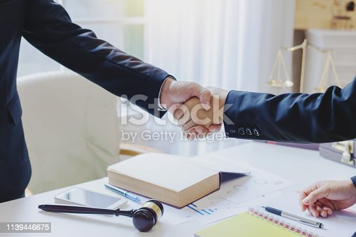 istock Businessman and lawyer shaking hands  to seal a deal with his partner. 1139446675