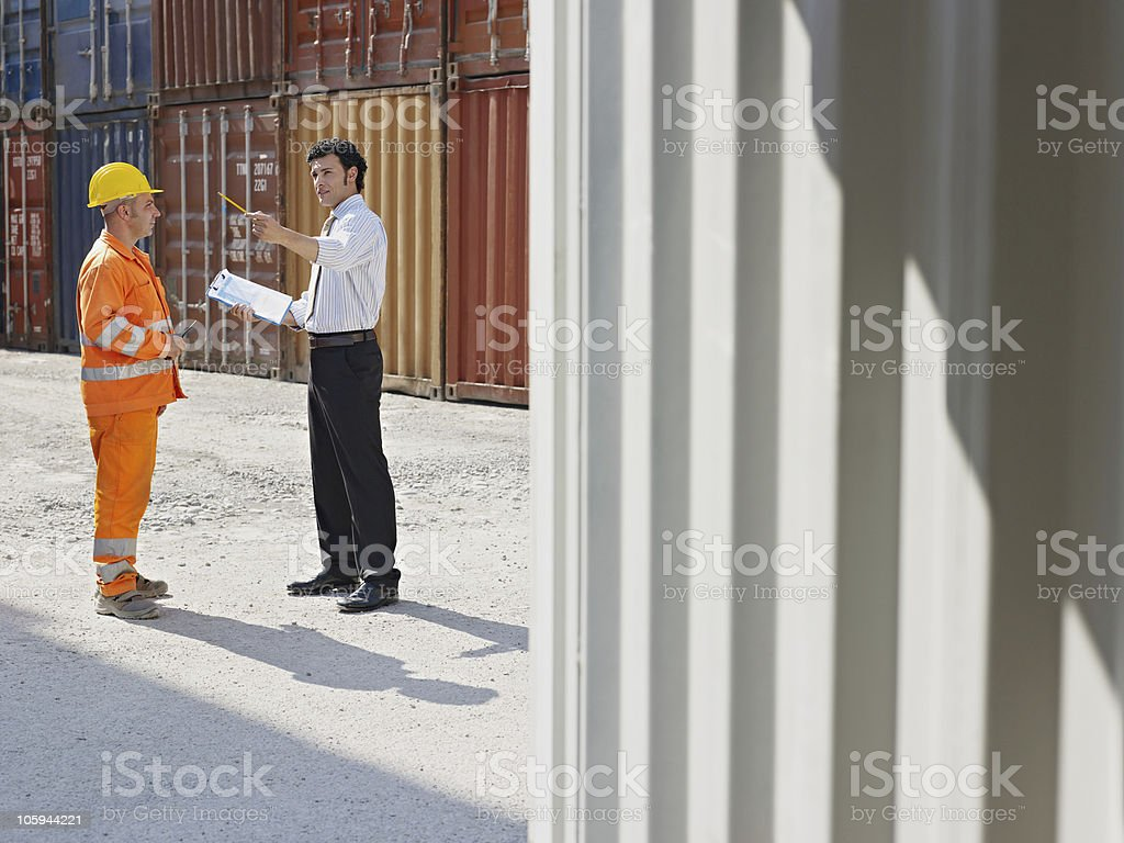 businessman and manual worker with cargo containers royalty-free stock photo