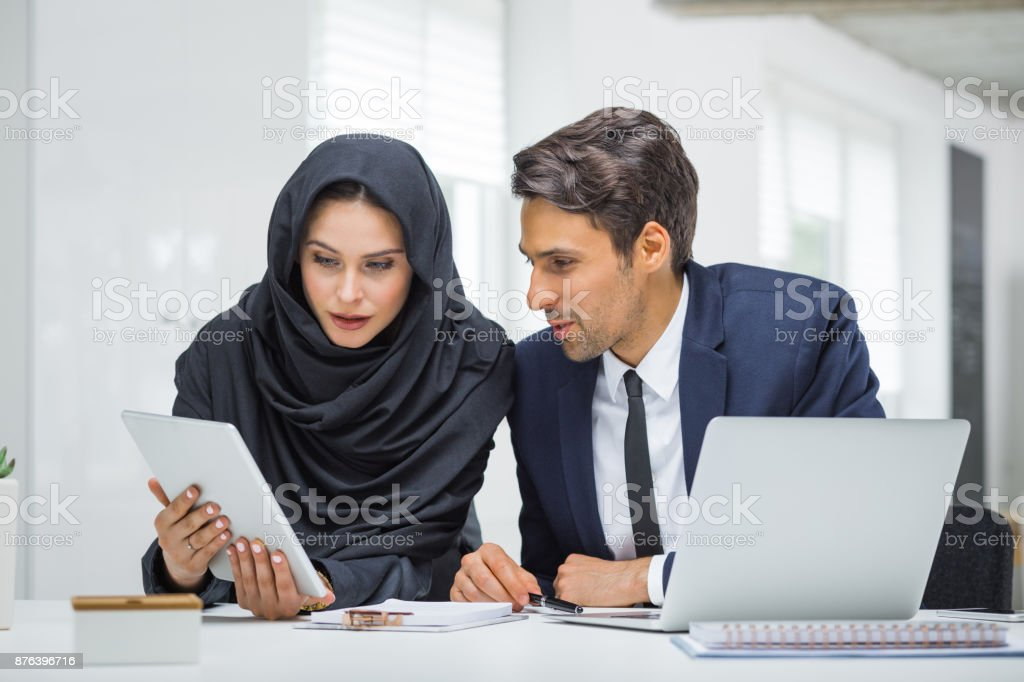 Businessman and muslim businesswoman working in office Young businessman and muslim businesswoman working together in office. Woman in hijab showing something on digital tablet to her male colleague. 20-29 Years Stock Photo