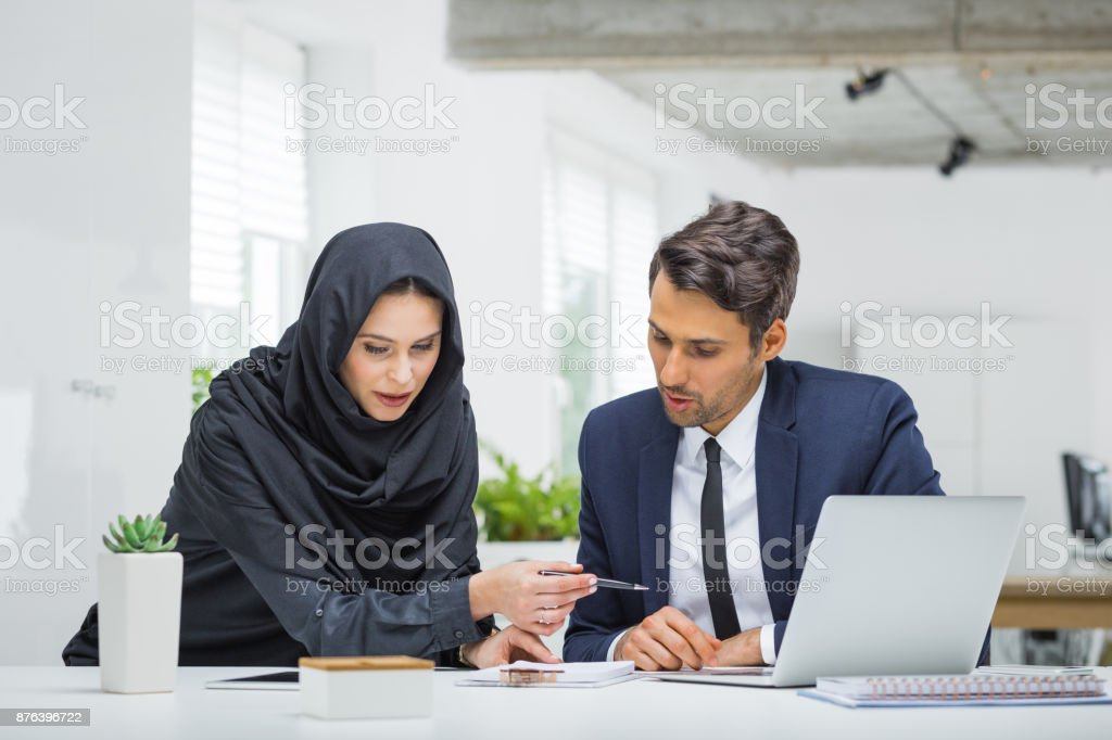 Businessman and muslim businesswoman working on project Businessman and woman working together on project at modern office. Muslim businesswoman and businessman looking at notepad and duscussing working strategy. Adult Stock Photo