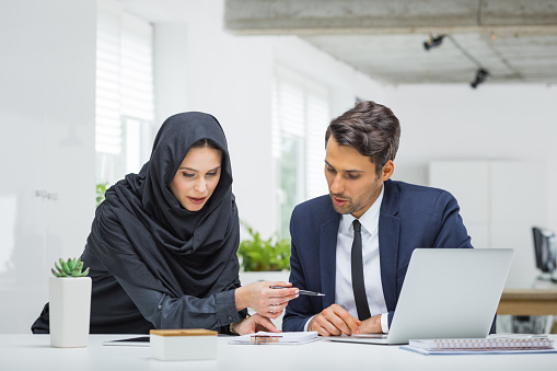 istock Businessman and muslim businesswoman working on project 876396722