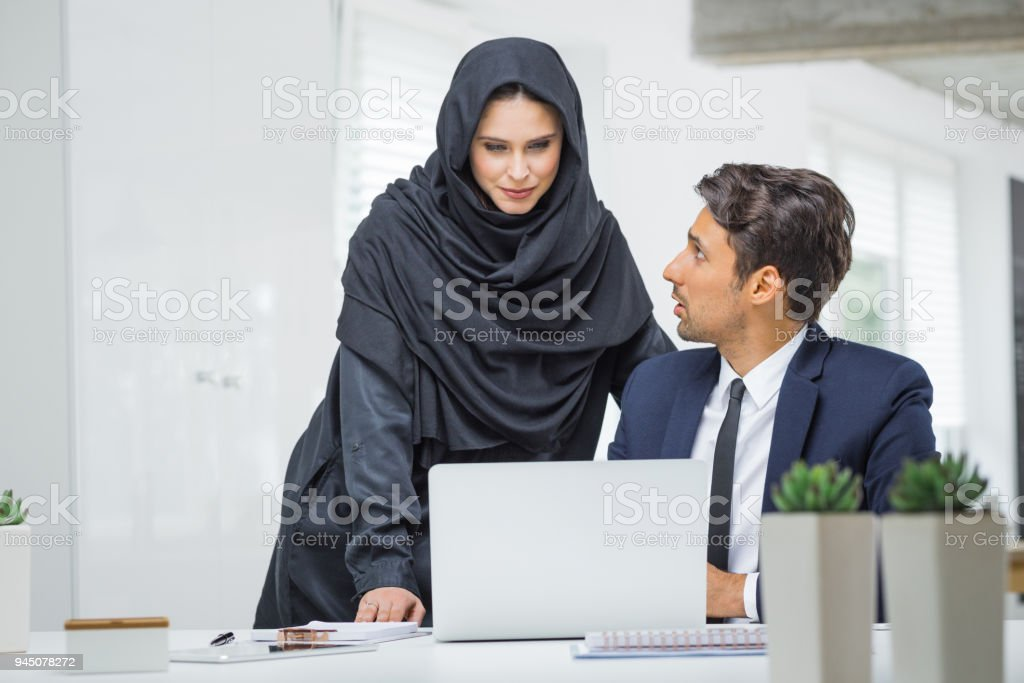 Businessman and muslim businesswoman working together in office Business couple working together on project at startup office. Muslim businesswoman in hijab with male colleague looking at laptop and discussing. Adult Stock Photo