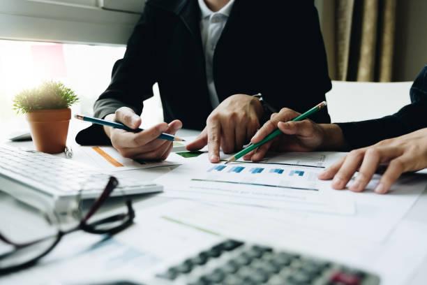 Geschäftsmann und Partner, die auf Graphen hinweisen, treffen sich, um den Verkauf zu planen, um die im nächsten Jahr gesetzten Ziele zu erreichen. – Foto