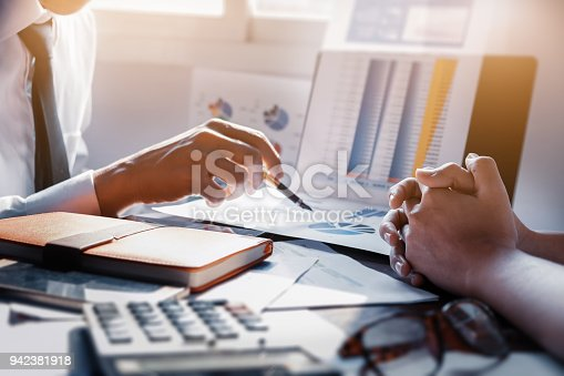 942382022istockphoto Businessman and partner pointing graph paper are meeting to plan sales to meet targets set in next year. 942381918