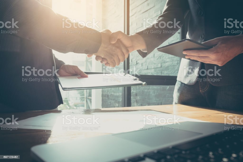 Businessman and partner shaking hands in office with vintage filter stock photo