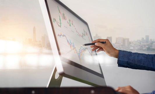 1025744818 istock photo Businessman and pen in hand analyzing sales data and economic growth graph on computer screen. Business strategy, stock market, Digital marketing. 1206797789