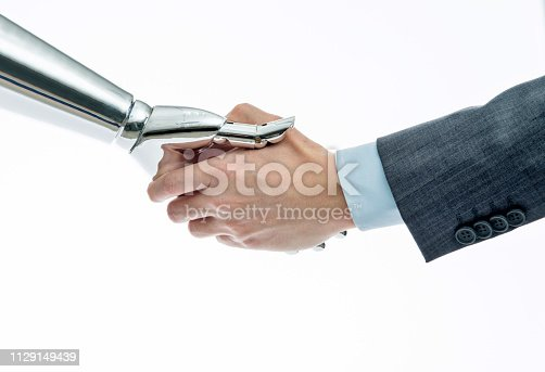 istock Businessman and robot shaking hands on white background 1129149439