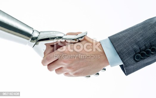 istock Businessman and robot shaking hands on white background 962162408