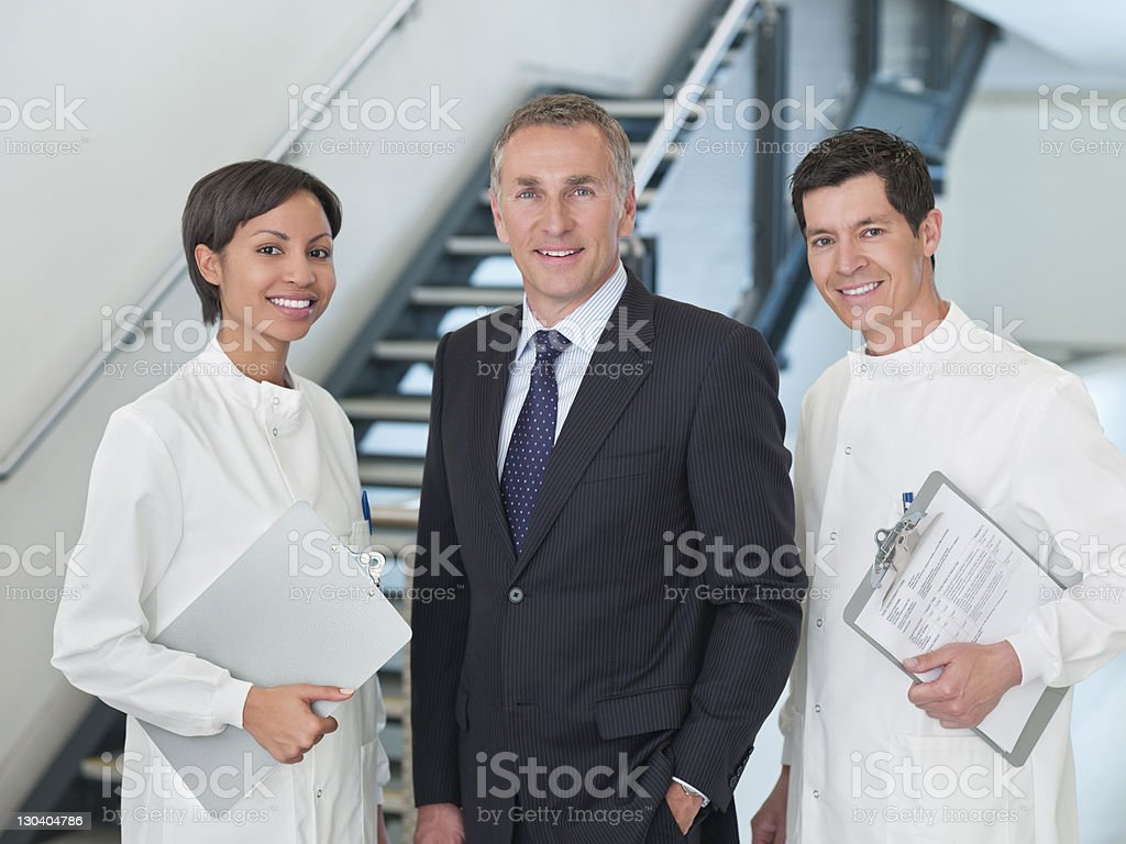 Businessman and scientists smiling together royalty-free stock photo