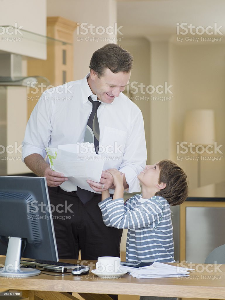 Businessman and son in home office stock photo