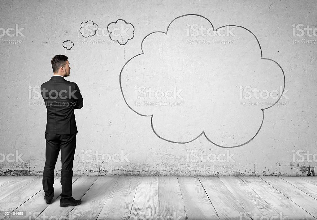Businessman and thought clouds on concrete wall background stock photo