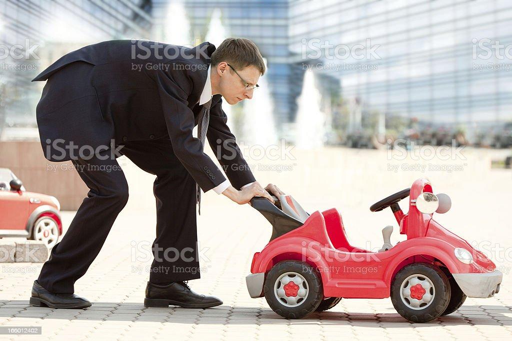 Empresário e Toy carro vermelho. - foto de acervo