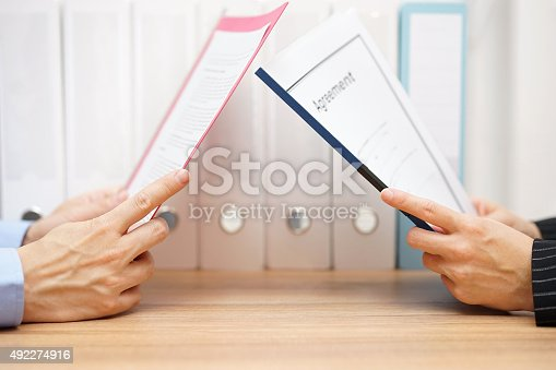 istock businessman and woman are reading agreement 492274916