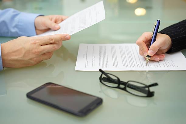 geschäftsmann und frau lesen und unterzeichnen vertrag - zeichen lesen stock-fotos und bilder