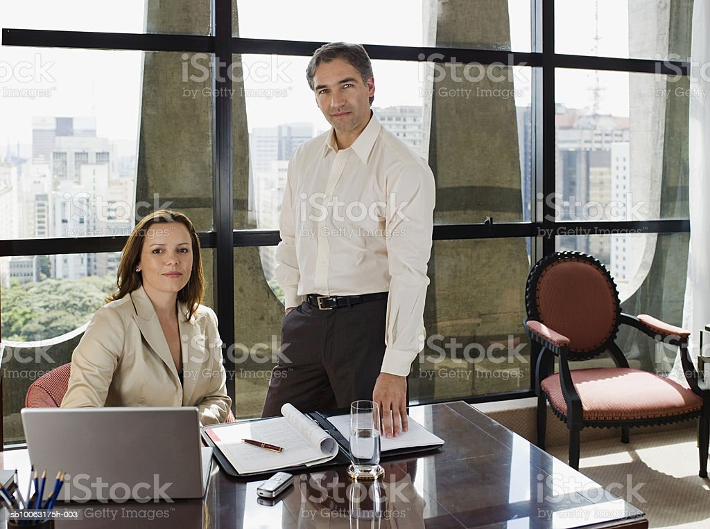 Businessman and woman at desk in hotel room, looking away, smiling foto de stock libre de derechos