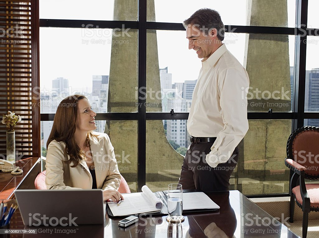 Businessman and woman at desk in hotel room, smiling foto royalty-free