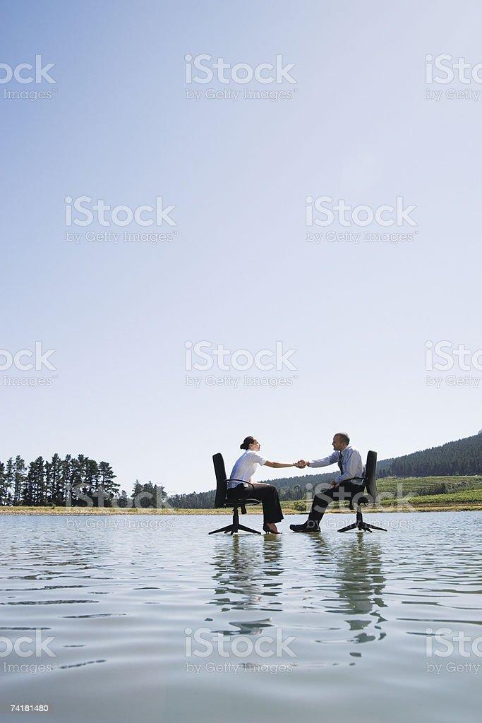 Empresário e mulher no escritório e cadeiras na água Balançando Mãos foto de stock royalty-free