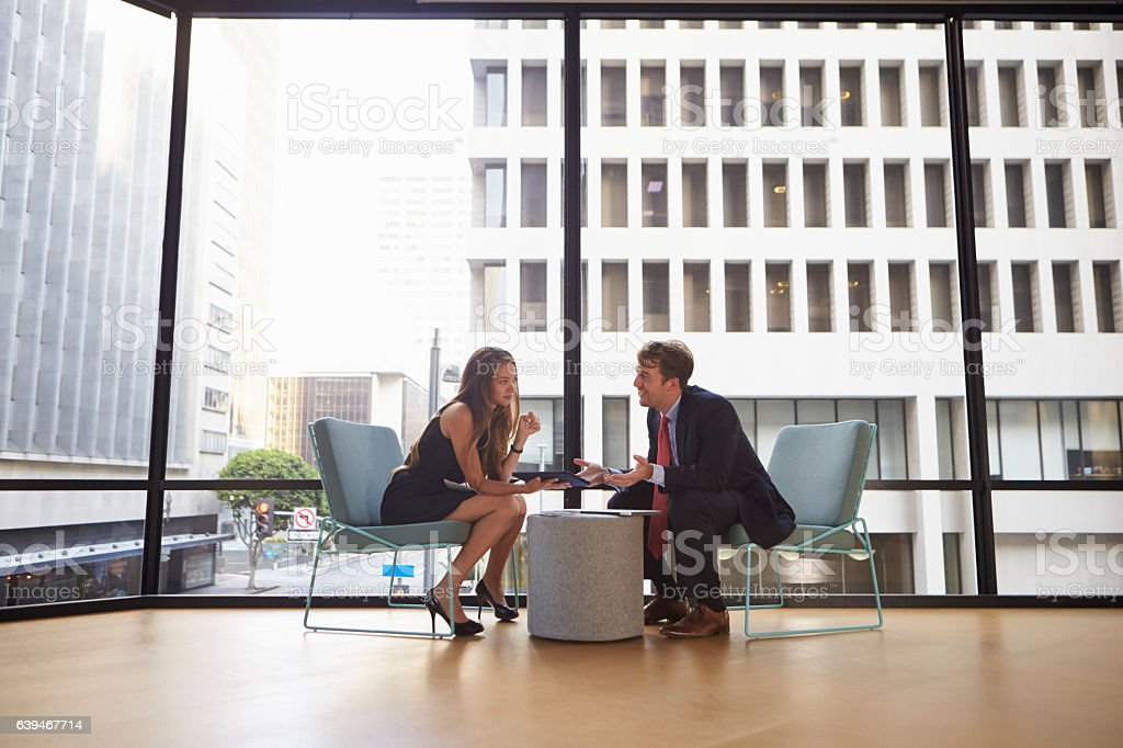 Businessman and woman meeting in modern office, full length stock photo