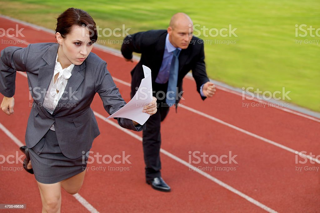 Businessman and woman on running on race track stock photo