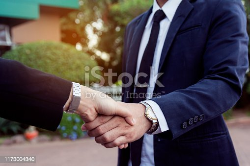 656005826istockphoto Businessman and woman shake hands after a business meeting 1173004340