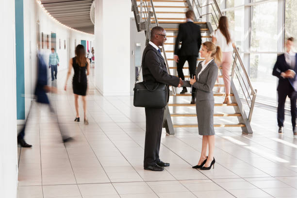 Businessman and woman shaking hands in a modern building stock photo